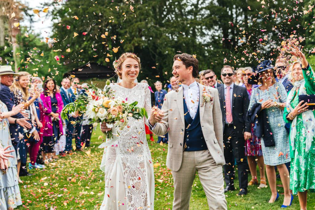 confetti exit at The Secret Walled Garden Wasing wedding. Bride wears grace loves lace