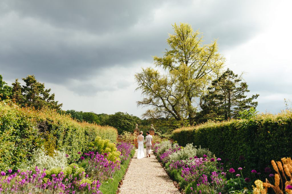 Bride and groom in garden at The Secret Walled Garden Wasing wedding. Bride wears grace loves lace