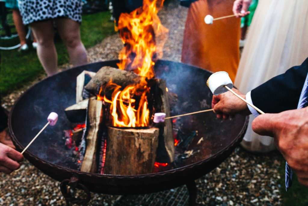 toasting marshmallows at The Secret Walled Garden Wasing wedding. Bride wears grace loves lace