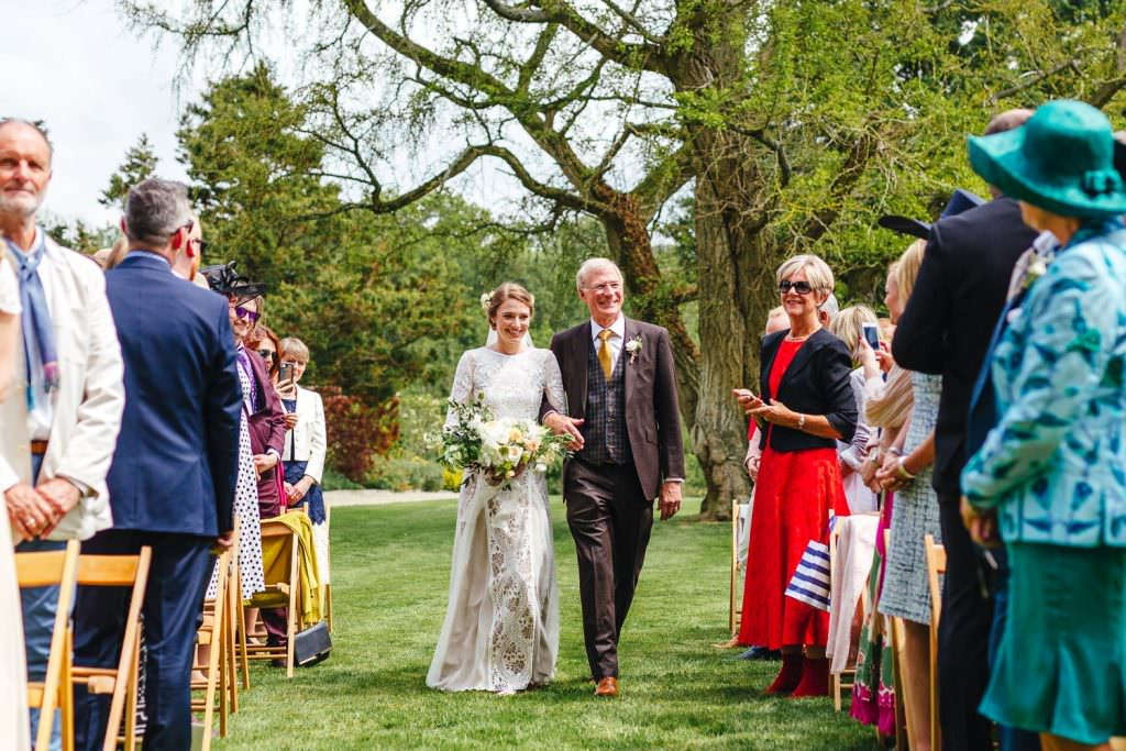 Bride and father walk down the aisle at The Secret Walled Garden Wasing wedding