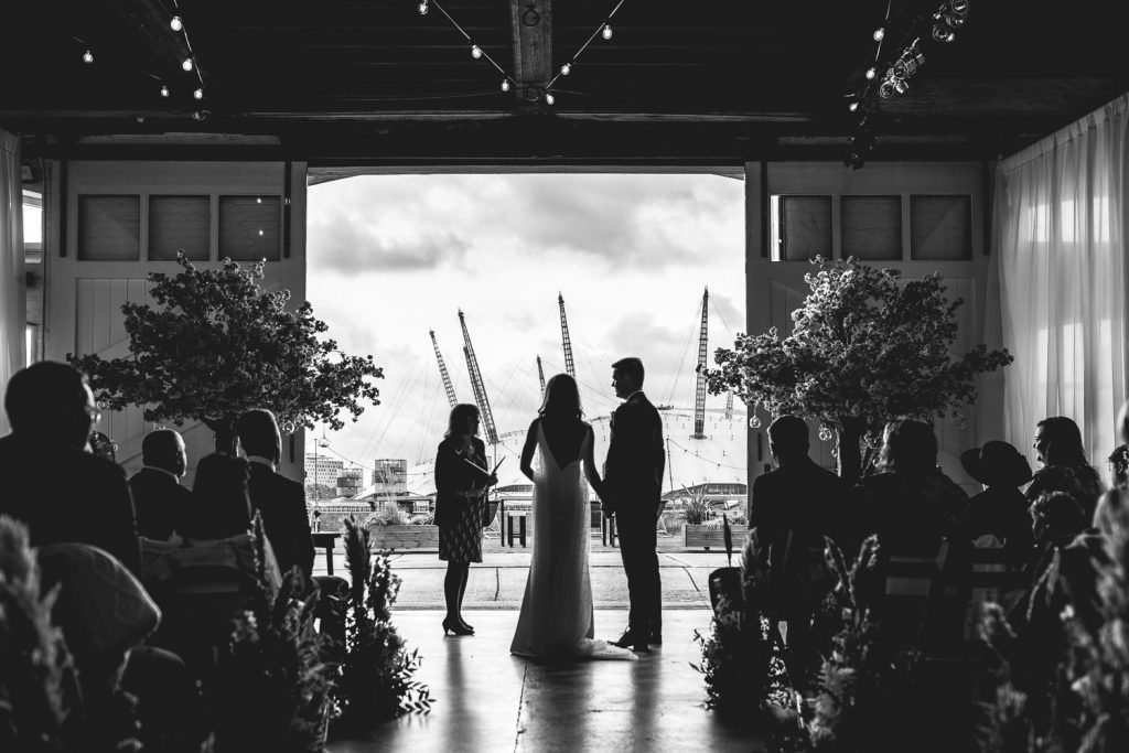 Ceremony with the thames and o2 in the background at Trinity Buoy Wharf Neon Wedding