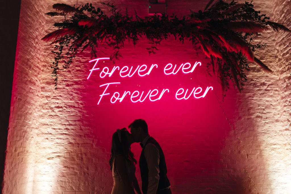 Epic neon sign with bride and groom at Trinity Buoy Wharf Neon Wedding