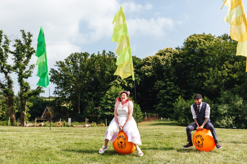 Bride and groom on space hoppers during wedding. Fun wedding photography at Frickley Lake.